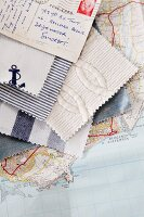 Fabric swatches in maritime styles and stamped postcard fanned out on top of map