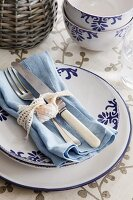 Place setting with blue-patterned china; old silverware and shell tied to pale blue napkin