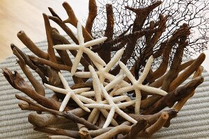 Dried starfish in original bowl of woven roots on wicker mat