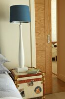 Maritime, blue and white bedside lamp on small steamer trunk; half-open sliding door in background of sleeping area