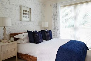 Wicker French bed with blue and white textiles against wallpaper with sailing boat motif