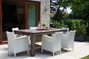 White wicker armchairs around large wooden table in front of open terrace doors in garden