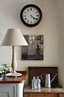 Wall clock with Roman numerals and small oil painting above tin watering can, wooden tray and glass bottles on wooden trunk lid next to table lamp with turned base on wooden sideboard