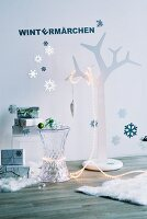 Stylised tree with fairy lights, plexiglass side table and stacked presents against wall with snowflake decorations