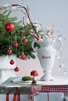 Christmas decorations hanging from branches in white, trophy-shaped china vase on table