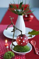 Christmas table centrepiece - decorated apple on bed of moss in dish and white china vase of twigs