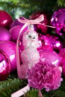 Pink Christmas tree baubles and dog figurine on fir branch