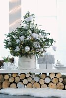 Christmas tree decorated with white baubles and presents on shelf resting on stacked logs