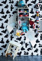Stool & toys on shelves against wallpaper with pattern of hand shadow animals