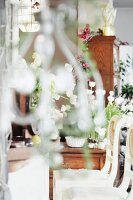 View into room with white chairs and decorated with bouquets