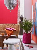 Ethnic shades of magenta and red in pleasant interior with wicker sofa