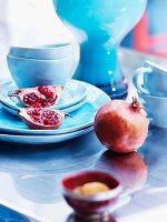 Pomegranates and pastel blue china crockery on shiny table top