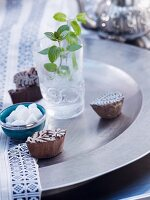 Sprig of peppermint in glass of water, sugar bowl and wooden printing blocks on metal dish