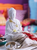 Buddha statue decorated with jewellery and silk scarf
