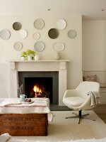 Vintage wooden trunk and pale swivel chair in front of open fire with decorative wall plates on chimney breast