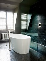 White, free-standing designer bathtub with standpipe tap fittings on dark mosaic floor next to shower area