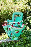Gardening utensils in turquoise plastic bag with cherry motif on stone wall in garden
