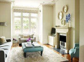 Ottoman on rug in front of sofa set extending into bay window of traditional living room with open fireplace