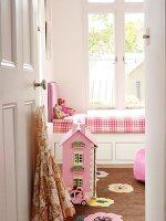 View through open door of dolls' house on floor in front of traditional child's bed below window