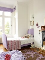 Lilac beanbag on patterned rug and sleigh bed with lilac fabric cover in front of bay window in child's bedroom