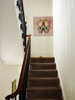 View up staircase with brown carpet and wrought iron balustrade to picture with shoe motif on wall of traditional staircase