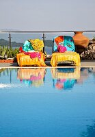 Colourful towels on loungers next to swimming pool on terrace (Villa Octavius, Lefkas, Greece)