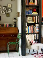 Green metal chair in front of antique bureau next to open doorway with view of white chair in front of bookcase