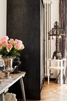 Silver, trophy-shaped vase of roses on wooden bench next to roller-door cupboard and iron lamp on side table
