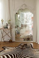 Side table next to antique mirror and zebra-skin rug on parquet floor in bedroom