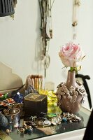 Rose in ceramic vase and vintage jewellery on side table