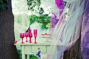 Erdbeertorte auf weissem Tisch zwischen Bäumen