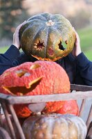 Person wearing a hollow pumpkin on their head