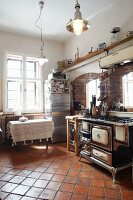 Country house with old kitchen cooker in front of brick archways and terracotta floor tiles