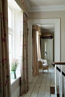 View from landing through open doorway into room with upholstered wicker armchair and antique, white wardrobe; floor-length curtains at windows add a pretty touch