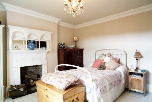 Feminine bedroom in traditional English style with elegant, white open fireplace, antique chest of drawers and stripped wood cabinet next to white metal bed