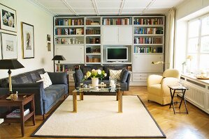 Sofa set and upholstered armchair around pale rug in front of fitted living room cabinets and shelving