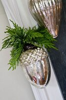 Christmas decoration of silver acorns with cypress sprigs