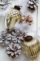 Silver Christmas decorations, pinecones and feathers