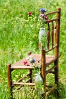 Bottles with wild flowers hanging on a wooden chair