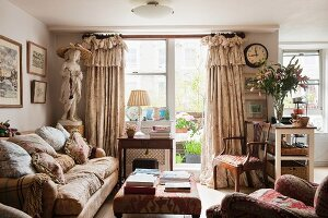 English living room with view of balcony; sumptuous valance curtains, many scatter cushions on sofa and statue of a girl create a nostalgic ambiance