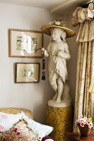Straw hat on head of statue of girl on pedestal in English living room between valance curtains and sofa with many scatter cushions