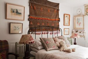 Woven tapestry, mainly in brown, and framed pictures above head of comfortable bed flanked by nostalgic bedside lamps on wooden chairs