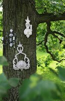 White, ornate candle sconces hung on tree in garden
