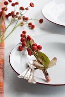 Place setting with name tag made from rosehips and leaves