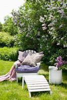 Soft cushions and blanket on garden chair beneath profusely flowering lilac and next to white-painted barrel used as side table