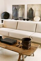 Rustic coffee table in front of a designer couch upholstered in light fabric and pictures on a sideboard leaning against the wall