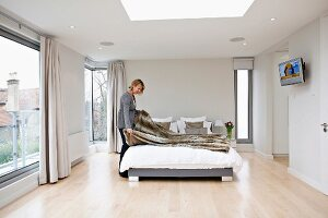 Woman making a bed in an elegant bedroom with floor to ceiling windows