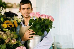 Male florist in his shop, holding a pot of pink roses
