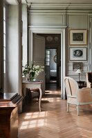 View through open interior doors of grand salon with antique side table below window and delicate armchair on herringbone parquet floor