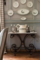 Candlesticks and antique jug on washstand with metal frame below plates and platters hung on grey-painted wooden wall